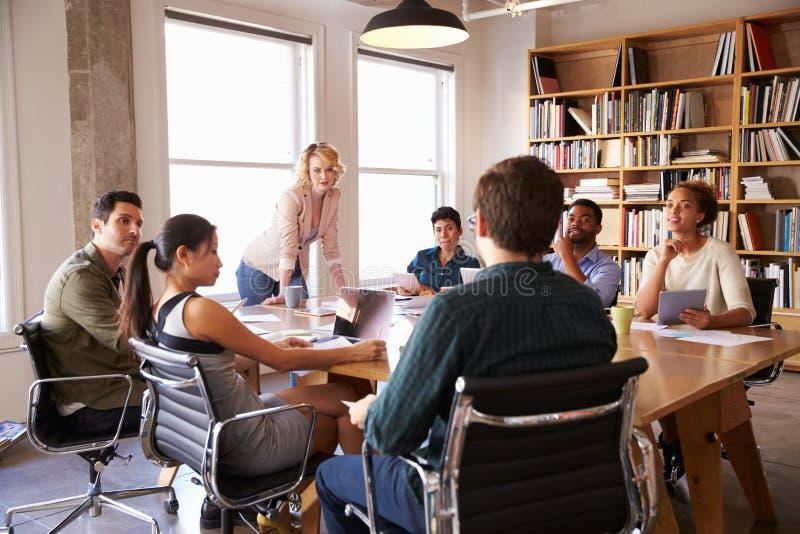 Mulher de negócios Addressing Team Meeting Around Table foto de stock