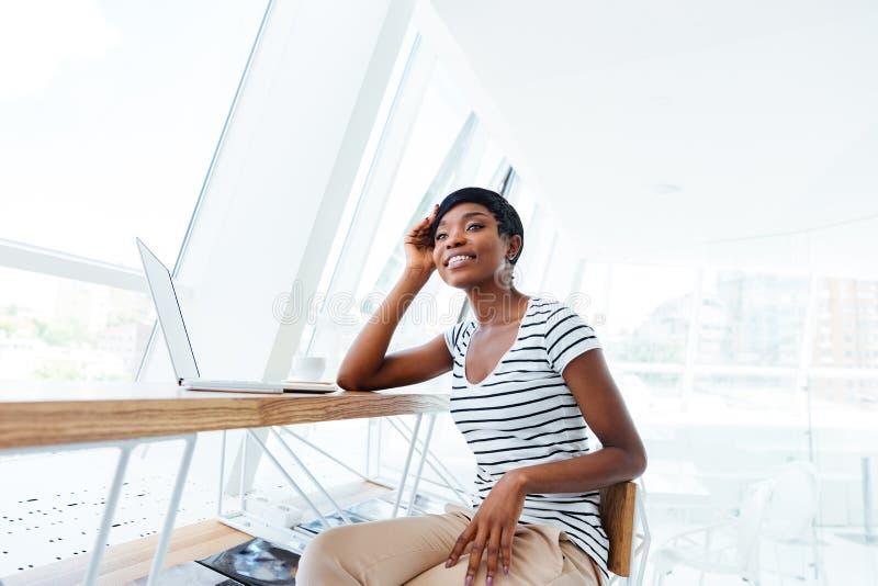 Mulher de negócios africana atrativa alegre que senta-se e que trabalha com portátil imagem de stock