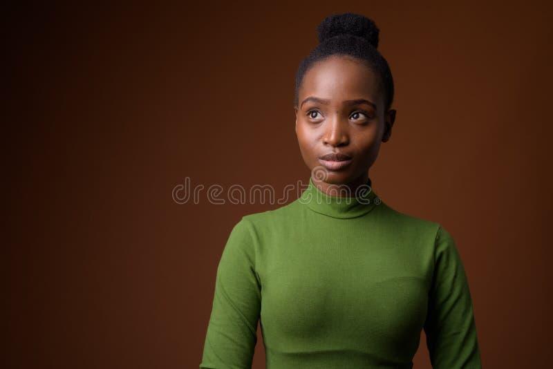 Mulher de negócios africana bonita nova do tribo Zulu que pensa e que olha acima imagem de stock royalty free