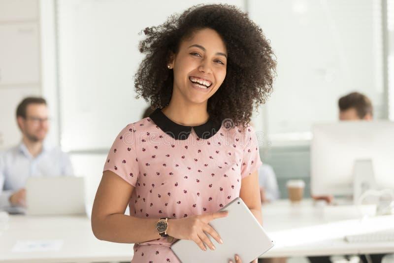 Mulher de negócios africana feliz que guarda a tabuleta digital que olha a câmera fotografia de stock