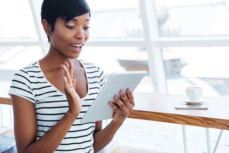 Mulher de negócios afro-americana feliz que guarda o tablet pc e a ondulação imagem de stock royalty free