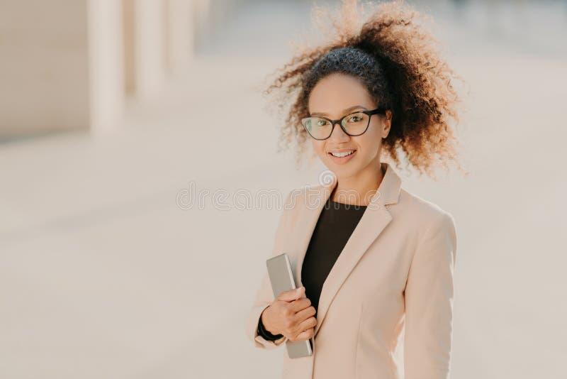 A mulher de negócios afro-americana lindo positiva dá uma volta exterior com touchpad, veste a roupa formal, espetáculos óticos,  imagens de stock royalty free