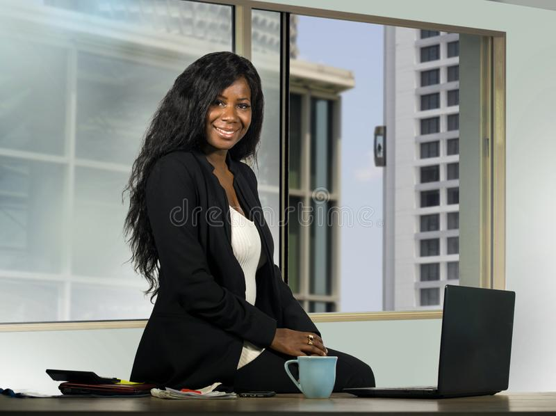 Mulher de negócios afro-americano bonita e feliz nova que levanta o funcionamento incorporado na mesa moderna do computador de es fotografia de stock