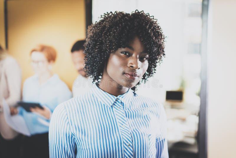 Mulher de negócios afro-americano bonita nova do retrato que está na frente dos colegas de trabalho no escritório moderno horizon imagens de stock