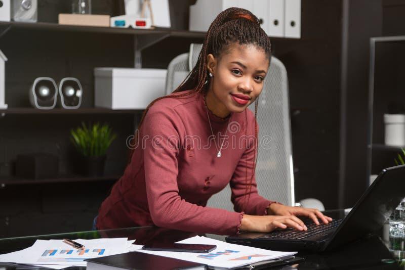 Mulher de negócios afro-americano nova que trabalha no portátil no escritório imagens de stock