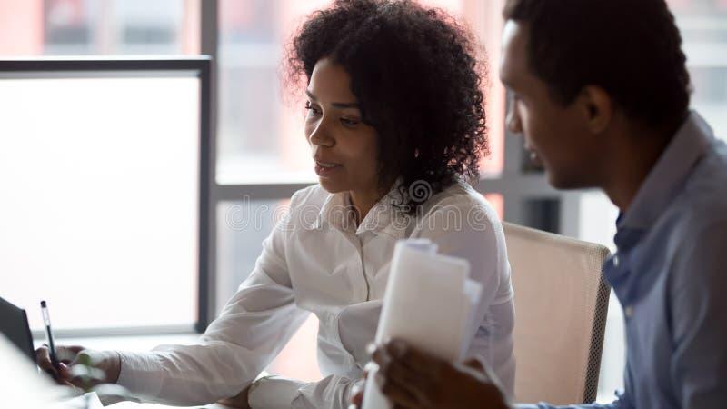 Mulher de negócios afro-americano que discute o projeto com o colega imagem de stock royalty free