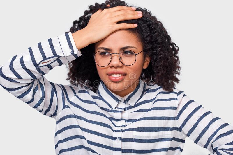 A mulher de negócios afro-americano tem a expressão do dilema, olha de sobrancelhas franzidas sua cara e olhando à câmera imagem de stock