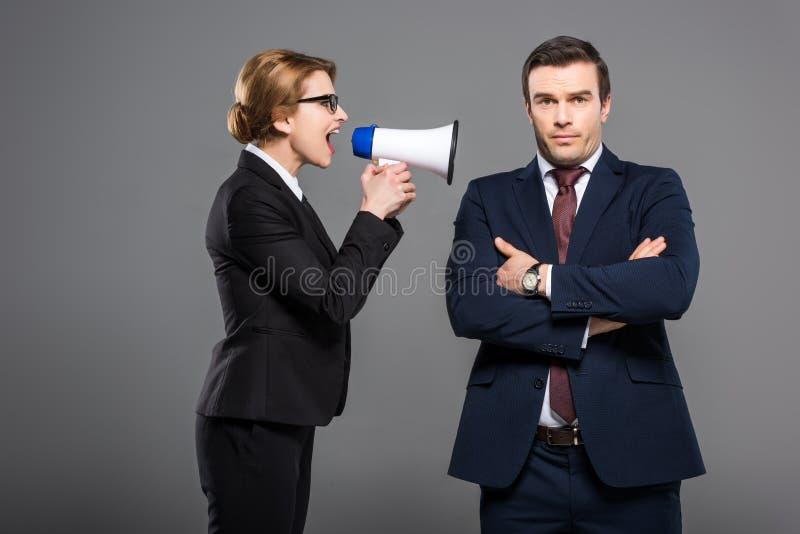 mulher de negócios agressiva com megafone que grita no homem de negócios, imagens de stock
