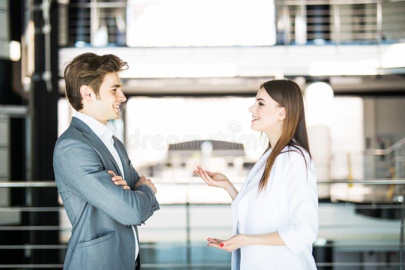 A mulher de negócios alegre explica a seu workmate que fala no escritório brilhante Conceito do negócio imagem de stock royalty free