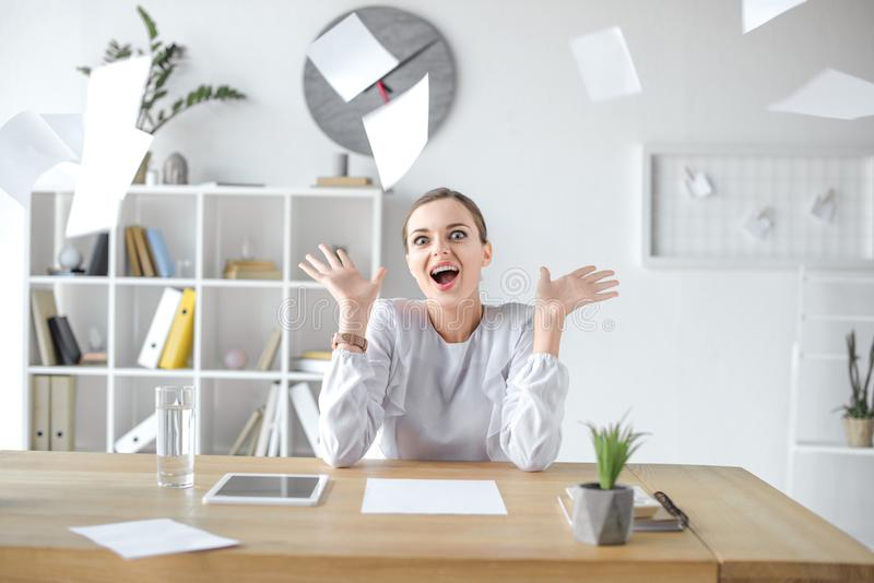 Mulher de negócios alegre que senta-se na mesa no escritório, quando as folhas de papel dispersadas voarem fotografia de stock royalty free