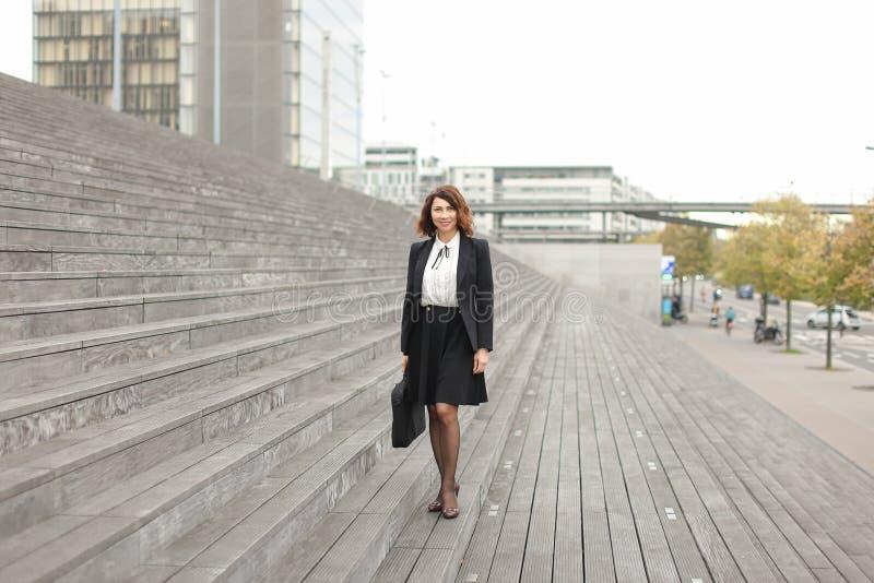 Mulher de negócios americana que está em escadas com saco e em construções altas no fundo imagem de stock