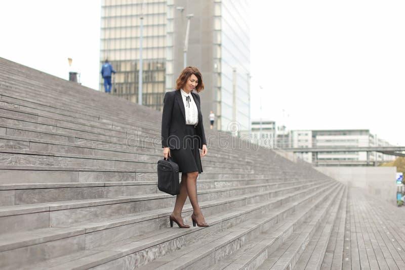 Mulher de negócios americana que tem o wearstyle clássico que vai para baixo em escadas no fundo alto das construções imagens de stock