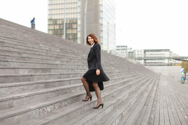 Mulher de negócios americana que vai acima em escadas no fundo alto das construções fotos de stock royalty free