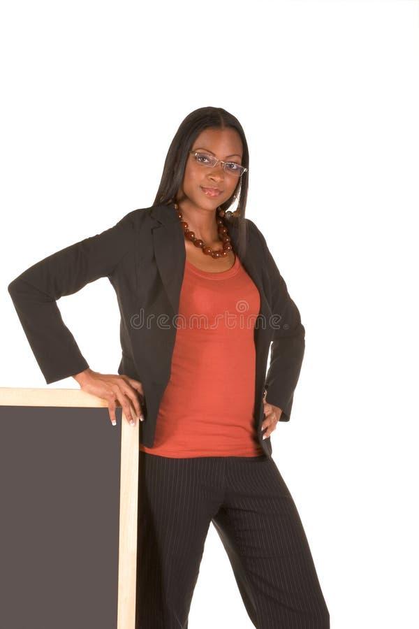 Mulher de negócios amigável que está pela placa de giz imagens de stock