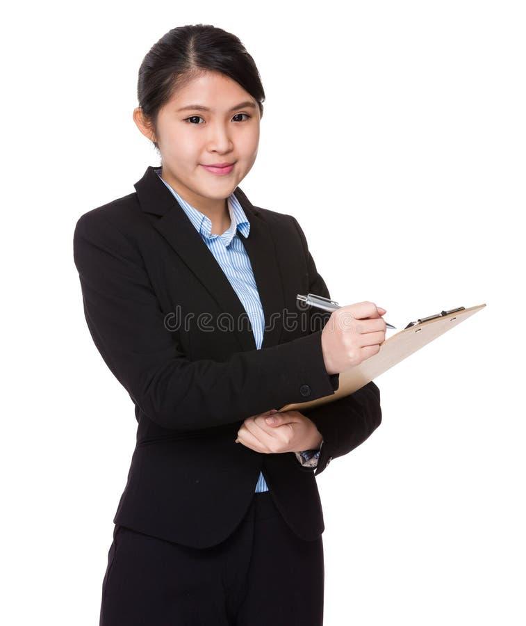 A mulher de negócios anota a nota o memorando na prancheta imagens de stock royalty free