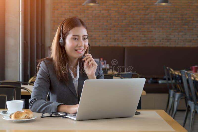 Mulher de negócios asiática bonita nova com os auriculares no café imagens de stock royalty free