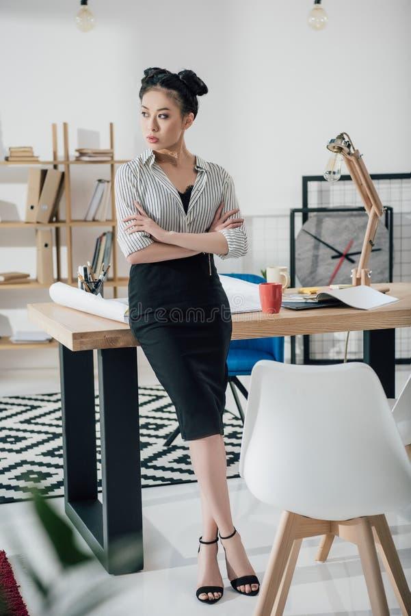 Mulher de negócios asiática com os braços cruzados que inclinam-se na tabela do escritório e que olham afastado foto de stock