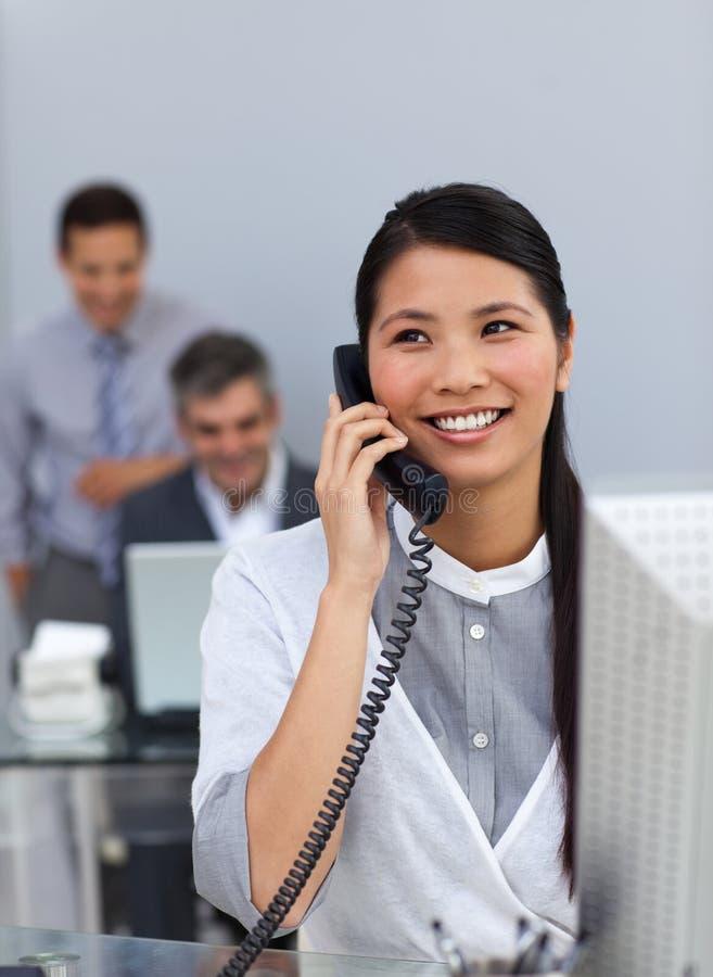 Mulher de negócios asiática confiável no telefone em sua mesa imagens de stock