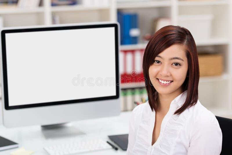 Mulher de negócios asiática de sorriso que usa um desktop