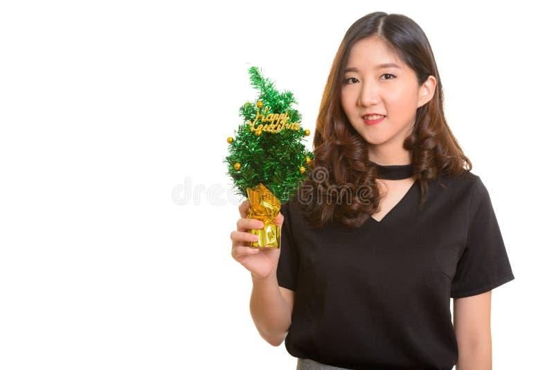 Mulher de negócios asiática feliz nova que guarda a árvore do ano novo feliz fotografia de stock royalty free