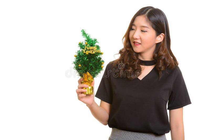 Mulher de negócios asiática feliz nova que guarda a árvore do ano novo feliz foto de stock