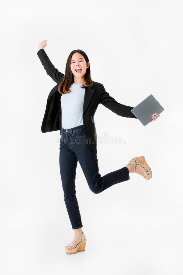 Mulher de negócios asiática no salto alegre do terno preto com celebratin fotografia de stock