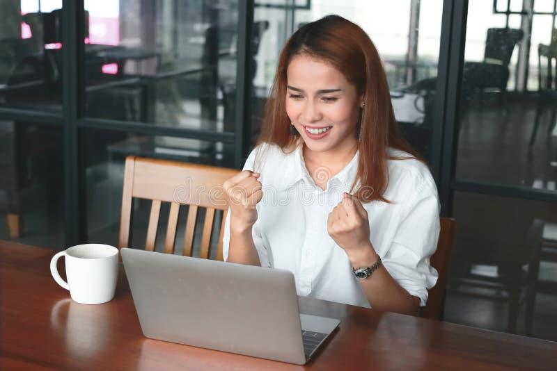 Mulher de negócios asiática nova alegre com portátil que sorri no local de trabalho no escritório Conceito bem sucedido do negóci imagens de stock royalty free