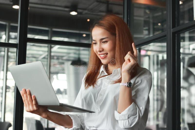 Mulher de negócios asiática nova bem sucedida com o portátil que tem ideias no escritório Pensamento e conceito pensativo do negó fotos de stock
