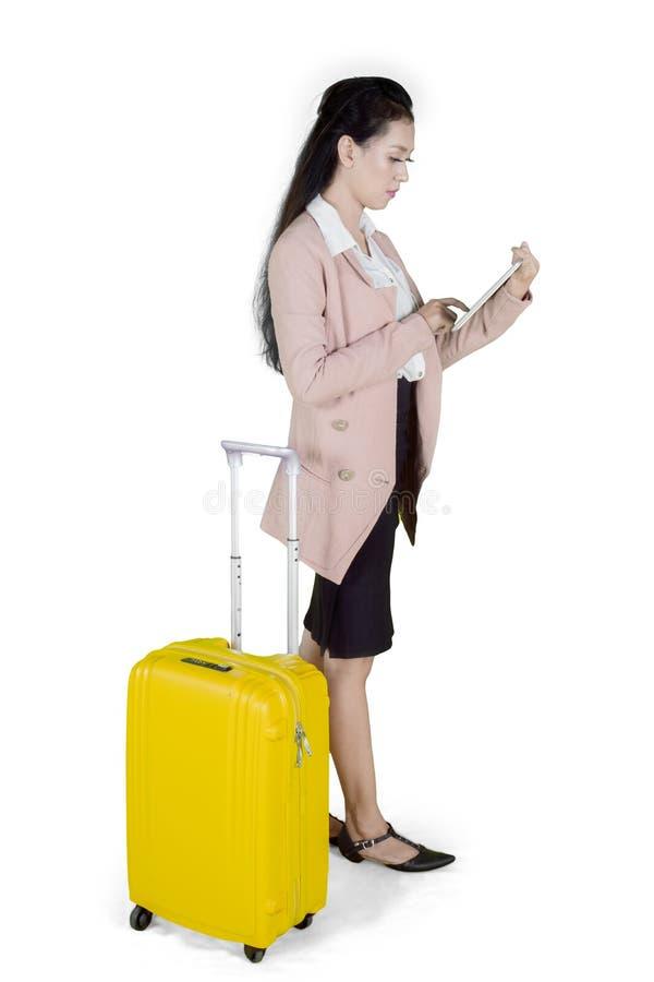 Mulher de negócios asiática nova com mala de viagem usando a tabuleta digital foto de stock royalty free