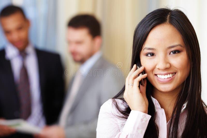 Mulher de negócios asiática nova no telefone imagem de stock