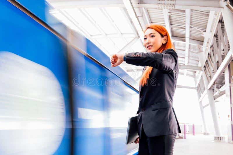 Mulher de negócios asiática nova no trem de espera do terno formal imagens de stock