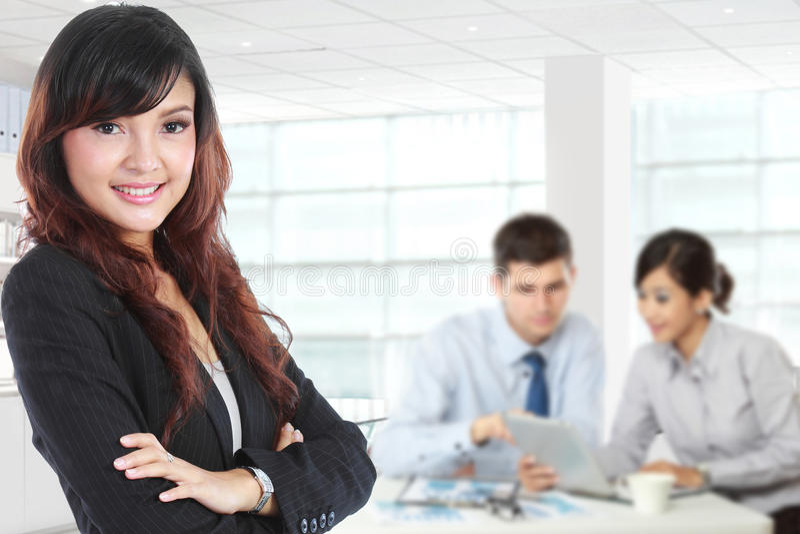 Mulher de negócios asiática nova que está com seu secretário atrás imagens de stock