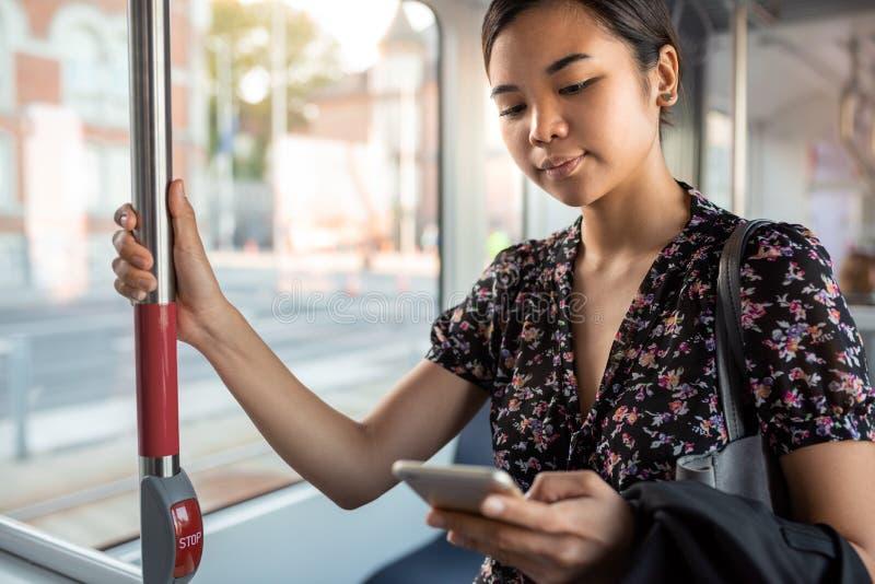 Mulher de negócios asiática nova que monta em um trem da cidade que lê textos imagem de stock royalty free