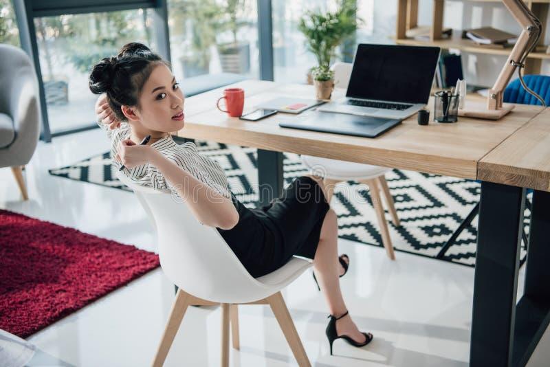 Mulher de negócios asiática nova que senta-se na tabela com portátil e que olha afastado foto de stock royalty free