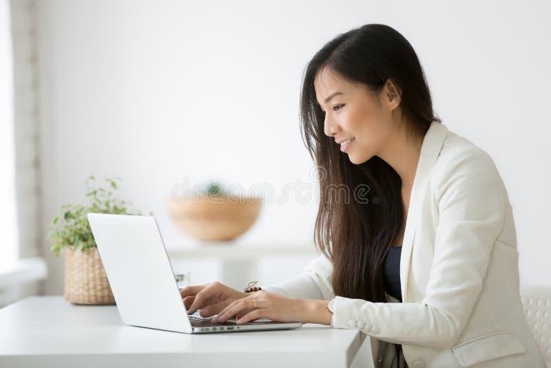Mulher de negócios asiática nova de sorriso que usa o computador que trabalha em linha imagens de stock royalty free