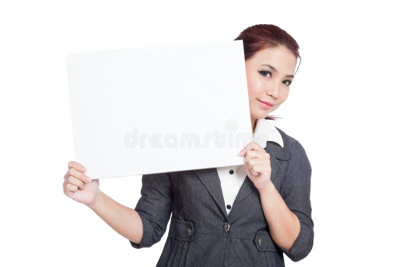 Mulher de negócios asiática que espreita atrás de um si vazio imagens de stock