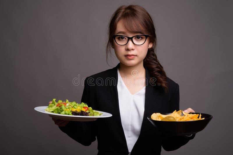 Mulher de negócios asiática que guarda microplaquetas da salada e de batata fotografia de stock royalty free