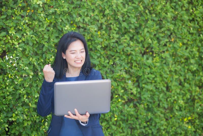Mulher de negócios asiática que guarda o caderno do computador e que mostra o polegar que faz acima o gesto aprovado fotos de stock royalty free