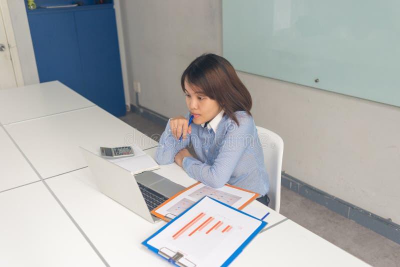 Mulher de negócios asiática que olha o portátil, pensando e tocando em seus bordos com pena foto de stock