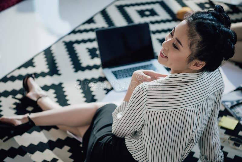 Mulher de negócios asiática que senta-se no tapete com portátil e que olha afastado imagem de stock royalty free