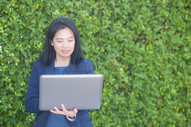 Mulher de negócios asiática que trabalha com o caderno do computador no ar livre fotografia de stock royalty free