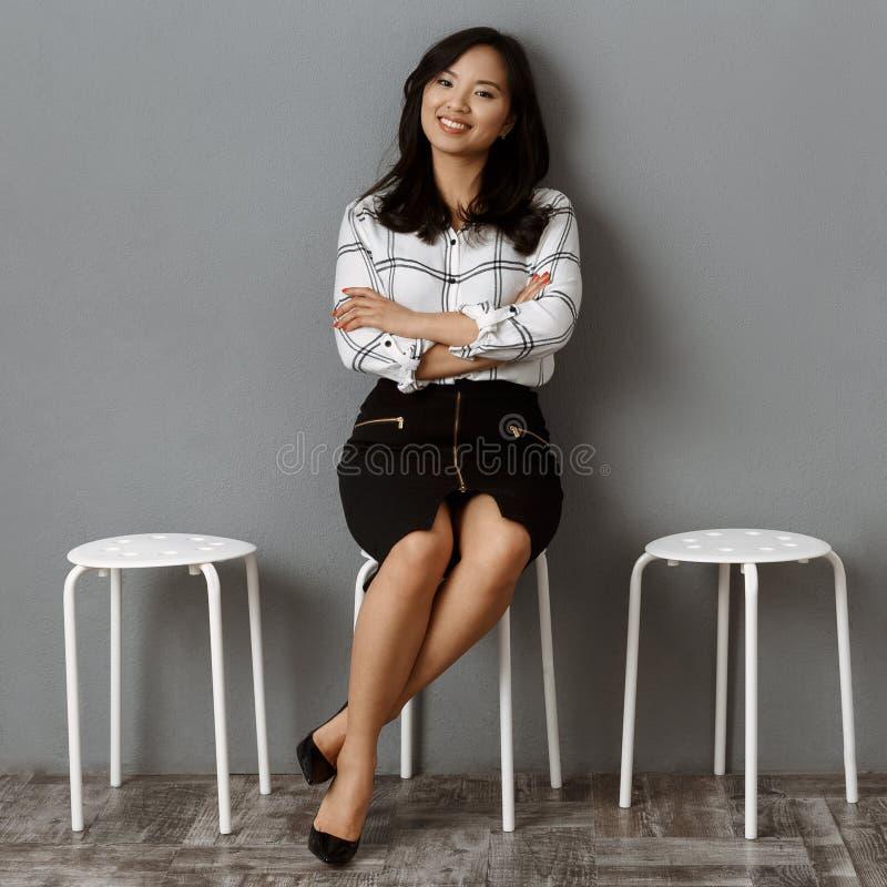 a mulher de negócios asiática de sorriso com braços cruzou a espera imagem de stock