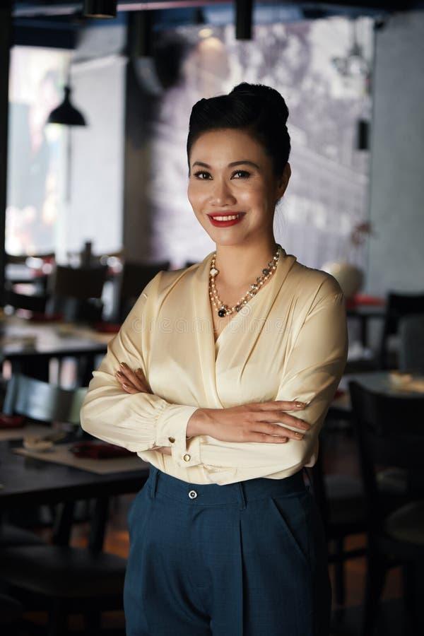 Mulher de negócios asiática de sorriso que está no café imagem de stock