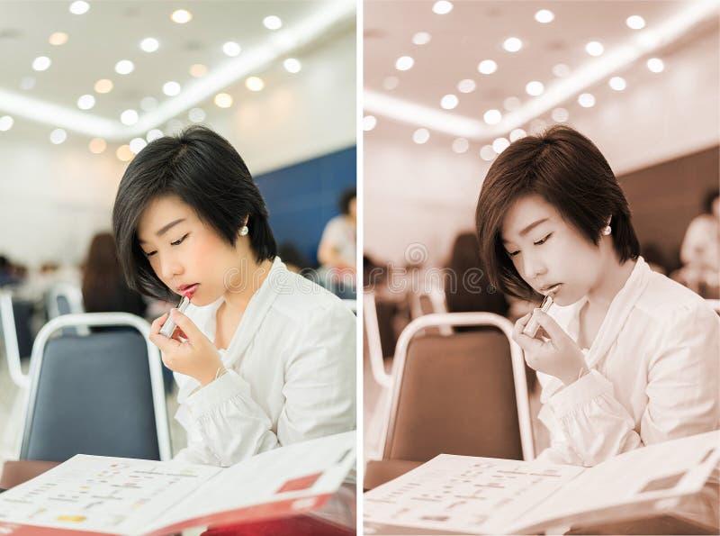 A mulher de negócios (asiática) tailandesa bonito está vestindo o batom no offic imagens de stock royalty free