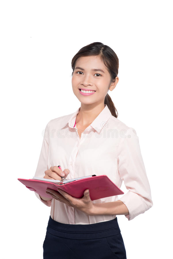 A mulher de negócios asiática toma a nota no caderno imagem de stock