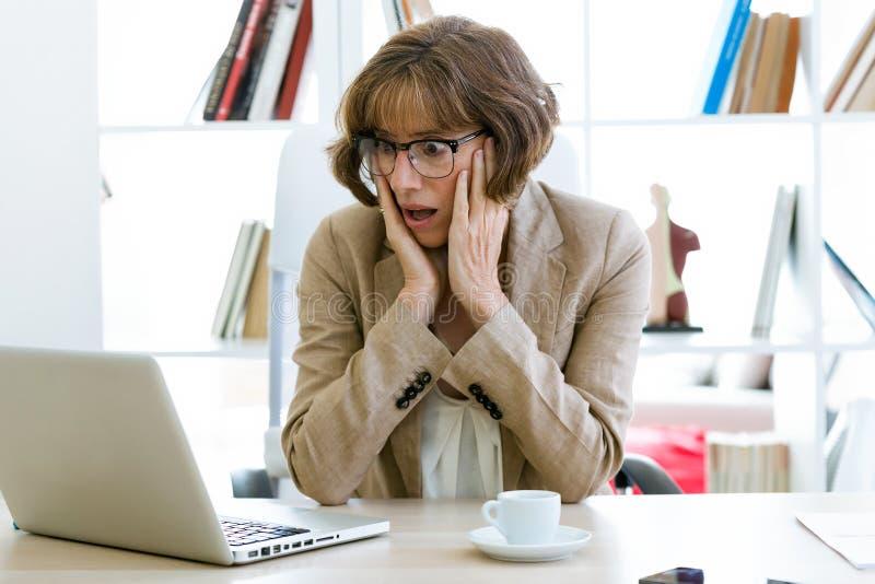 Mulher de negócios assustado e preocupada que olha algo em seu portátil na mesa no escritório imagem de stock