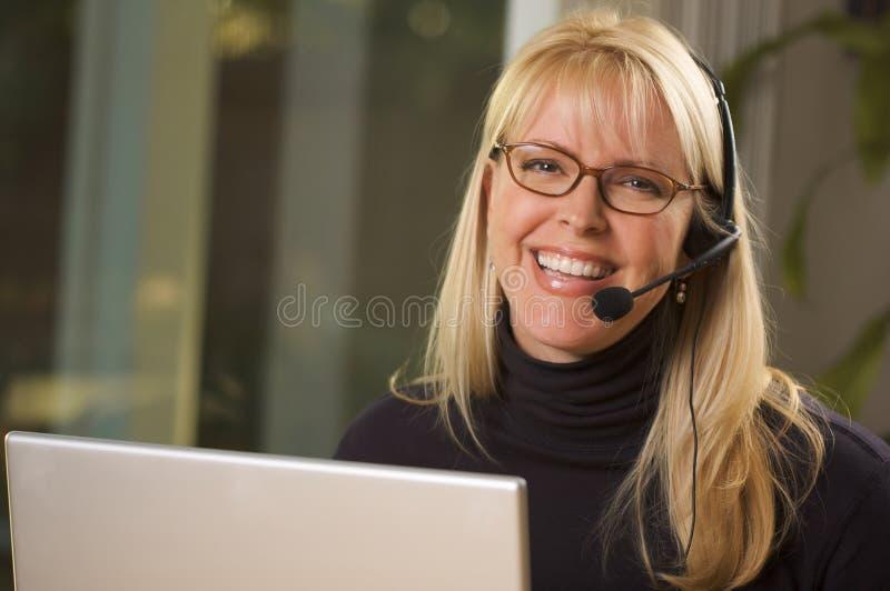 Mulher de negócios atrativa com auriculares do telefone fotografia de stock
