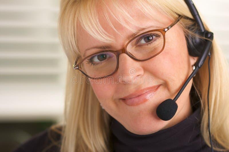 Mulher de negócios atrativa com auriculares do telefone foto de stock
