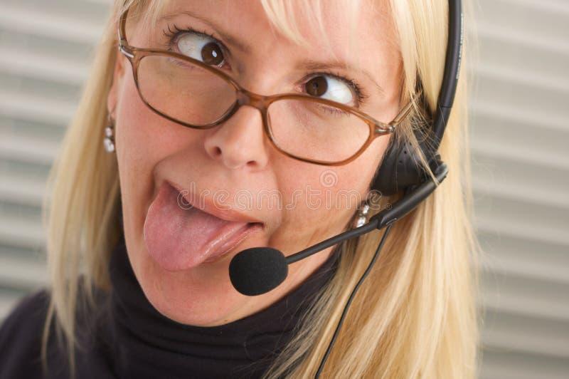Mulher de negócios atrativa com auriculares do telefone fotografia de stock royalty free