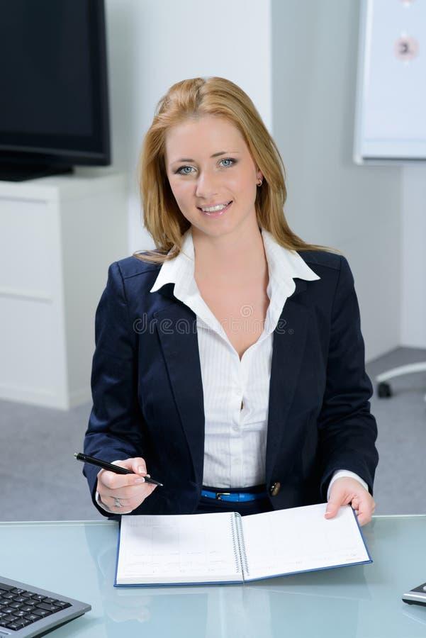 Mulher de negócios atrativa em sorrisos do escritório fotografia de stock royalty free